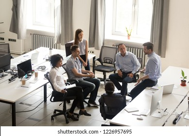 Serious ceo speaking at corporate group meeting, teacher coach team leader talking to office workers interns students at corporate training teaching explaining project strategy, mentoring, top view