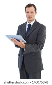 Serious charismatic businessman holding a tablet computer on white background