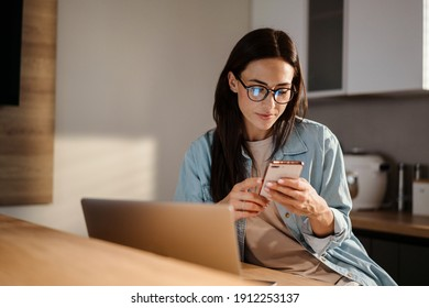 Serious charming woman using smartphone while working with laptop at home