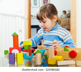 serious child playing with toys in home interior