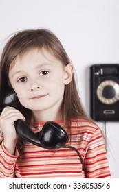 Serious child talking on phone, white background