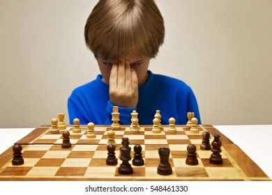 Serious clever boy looking at chess board and thinking about next move. Game, education concept