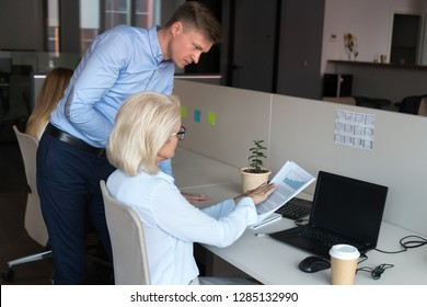 Serious company ceo mature businesswoman sitting at desk talking with employee male worker pointing on mistakes in financial report or sales statistics, having questions claims to agreement conditions