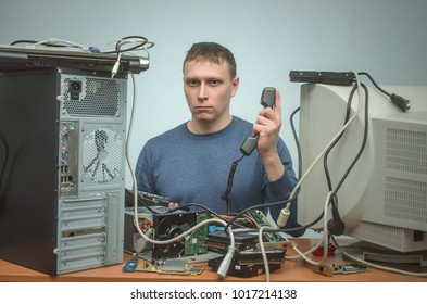 Serious Computer technician is consulting a users by their questions by the phone. PC repair service center.
