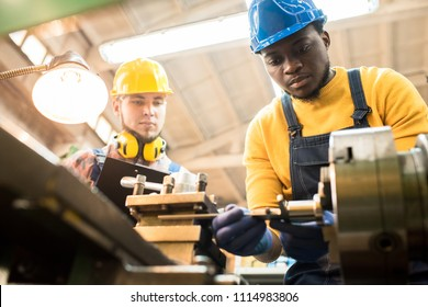 Serious concentrated African-American factory engineer in hardhat adjusting milling machine and joining detail while skilled inspector examining his work and controlling production process