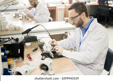 Serious concentrated bearded male engineer in safety goggles producing monitoring and measuring device in modern workshop of pressure transducer plant