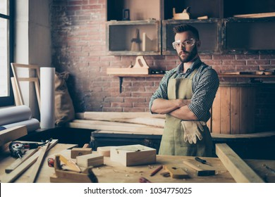 Serious concentrated confident qualified handsome bearded cabinet-maker wearing apron and safety glasses is standing with crossed arms in his workshop and going to work with wood