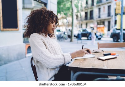 Serious concentrated dark skinned woman sitting on cafe terrace writing article for homework task, concentrated african american female creative designer doing sketches and drawings for plan project