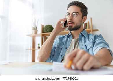 Serious concentrated fashionable male office worker calls to colleague on cellular, has phone talk, try to arrange meeting discuss everything alive. Creative male designer shares idea with companion