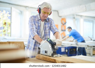 Serious concentrated gray-haired mature carpenter in checkered shirt standing at workbench and cutting wooden plank with circular saw in modern workshop