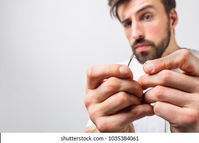 Serious and concentrated guy is trying to put a thread through an eye of a needle. He is doing that very accurate. Close up. Cut view. Isolated on white background.