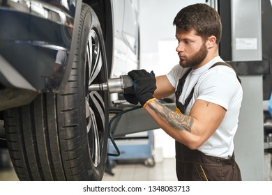 Serious, concentrated mechanic changing, repairing wheel hubcap, using special equipment. Bearded, muscular man in white t shirt fixing vehicle in garage autoservice.