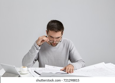 Serious concentrated office worker being focused on writings and preoccupied, look through spectacles, sits at cozy office, use modern tablet for work, studies blueprint attentively on drawing table
