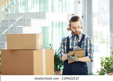 Serious concentrated skilled moving foreman writing necessary information in sketchpad while analyzing packages in storehouse