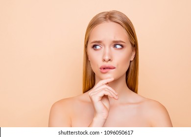 Serious, concentrated, thoughtful, attractive woman holding hand on chin looking to the side with eyes trying biting low lip with teeth, isolated on beige background wellness wellbeing concept
