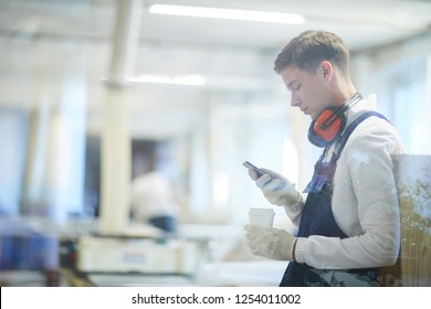 Serious concentrated young construction worker in ear protectors and work gloves standing in workshop and using gadget while drinking coffee at break