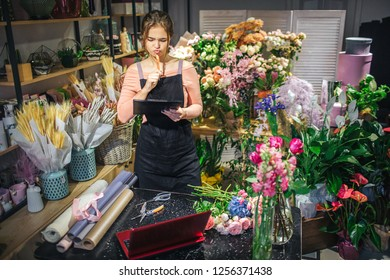 Serious and concentrated young florist hold black planchette. She think and look at it. Floris is surround with flowers and plants. Paper rolls and red laptop are on table.