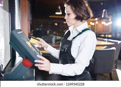 Serious concentrated young waitress with short hair standing at restaurant desktop computer and using plastic card while choosing dish on POS terminal
