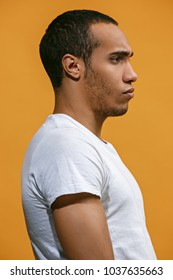 Serious concept. Serious Afro-American man is looking serious. Young emotional man. Human emotions, facial expression concept. Profile . Studio. Isolated on trendy orange