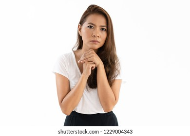 Serious concerned young woman clasping hands at chin and looking at camera. Worried girl waiting for important news or asking for help. Anxiety concept