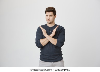 Serious confident angry european man with stubble in casual clothes, keeping hands in stop gesture, crossing arms, frowning his face, as if saying: Stop that. Body language.