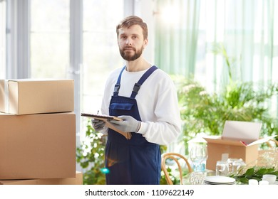 Serious confident bearded young male mover in overall and gloves holding sketchpad and looking at camera while checking delivered goods in new restaurant