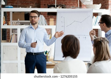 Serious confident business coach gives presentation on flipchart training workers group, executive presenter team leader explaining graph on whiteboard teach sales team employees at corporate meeting