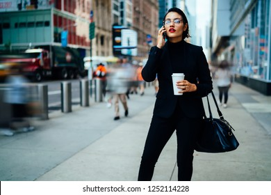 Serious confident business woman in elegant black suit and optical eyewear calling to partner for discussing time of meeting in financial district using roaming connection on modern mobile phone