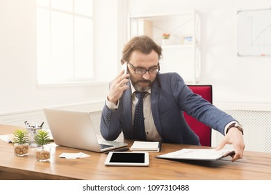 Serious confident businessman talking on mobile phone and reading report in modern white office, copy space