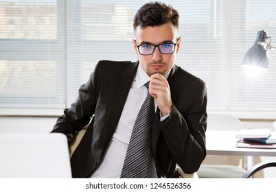 Serious confident businessman working in office, sitting at desk, looking at camera.
