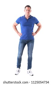 Serious confident fit man in casual clothes with hands on hips looking at camera. Full body isolated on white background.