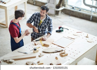 Serious confident handsome middle-aged man with beard standing at desk and drilling wooden detail while showing intern with sketchpad how to make hole in wooden piece.