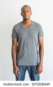 Serious confident handsome young African man in casual clothing standing and looking at camera. Upset guy wearing gray t-shirt and jeans. Individuality concept