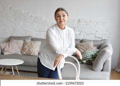 Serious confident mature female wearing blouse and trousers standing behind chair with hands on its back, posing in the middle of modern living room with comfortable large couch in background