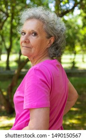 Serious confident old lady walking in park. Side and back of senior grey haired woman in casual turning face to camera. Senior woman outdoors concept