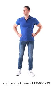 c7cc2c628917 Serious confident young adult casual man in blue polo shirt looking away  with arms on hips