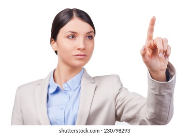 Serious and confident.  Confident young businesswoman touching a transparent wipe board while standing against white background
