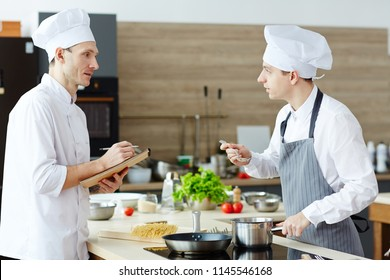 Serious confident young chef in white uniform making notes in sketchpad while testing intern cook who tasting sauce at commercial kitchen