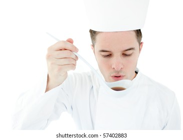 Serious cook tasting a soup against white background