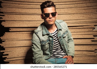 serious cool casual man wearing sunglasses and sits against wooden studio background