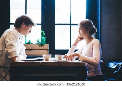 Serious couple 20s discussing problems in relationship while sitting at cafeteria table with coffee cups, young caucasian male and female talking during leisure time in cafe with loft interior