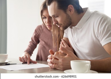 Serious couple studying contract agreement, reading terms and conditions attentively before signing, husband and wife calculating domestic bills, considering mortgage loan offer, health insurance
