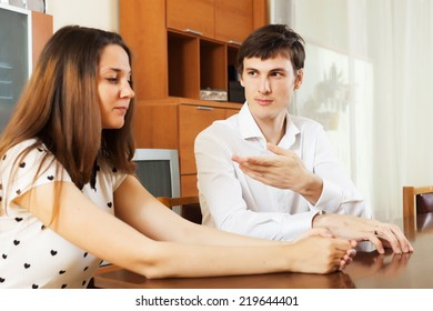 Serious couple talking in home interior. Focus on man