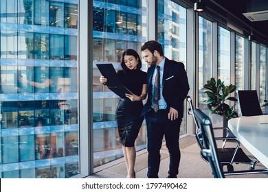 Ernsthafte Mitarbeitende in eleganter Kleidung, die durch moderne Büros gehen und gemeinsam Berichte lesen, während sie an einem Projekt arbeiten