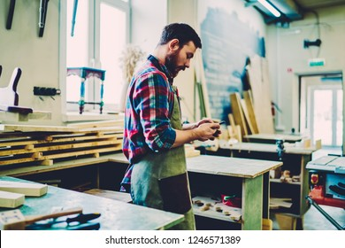 Serious craftsman in apron checking message with orders on smartphone owning restoration store, young handsome male carpenter using smartphone for checking banking balance online while work