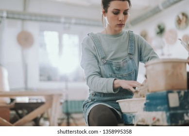 Serious craftswoman in denim overalls preparing raw clay for pottery. Copy space in left side