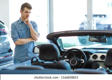 Serious customer standing near new folding top car in auto show room, looking at car interior and examining carefully vehicle. Handsome male in checkered shirt keeping hand near chin and thinking.