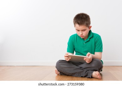 Serious Cute 10 Year Old Young Boy Sitting on the Floor with Legs Crossed, Busy with his Tablet Computer