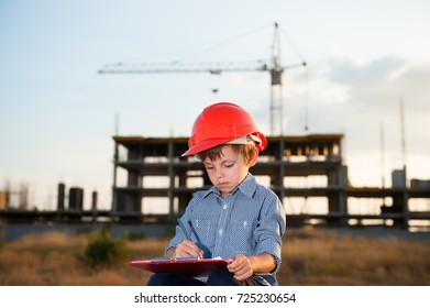 serious cute little boy in an orange helmet and shirt makes corrections in the design on background of a building with a crane