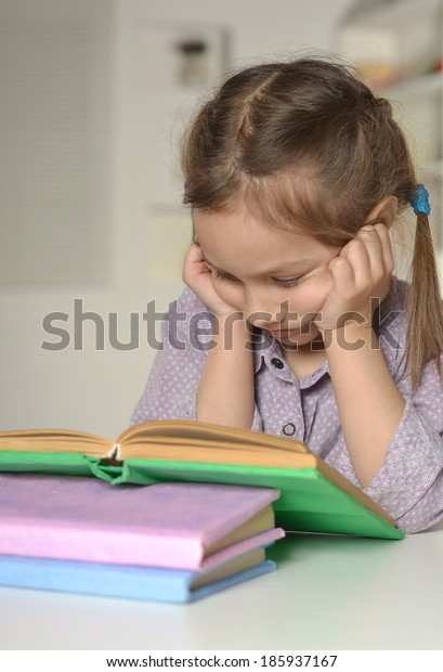 Serious cute little girl with a book